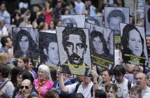 People carry photos of victims of the 1976-83 dictatorship, during a march marking the 40th anniversary of the military coup in Buenos Aires, Argentina, Thursday, March 24, 2016. In the first visit for a U.S. president in nearly 20 years to Argentina, President Barack Obama coincided with the anniversary of the 1976 coup, stirring up lingering questions about America's role supporting the military dictatorship that followed. (AP Photo/Victor R. Caivano)
