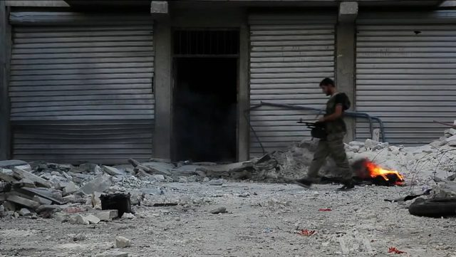 free_syrian_army_soldier_walking_among_rubble_in_aleppo
